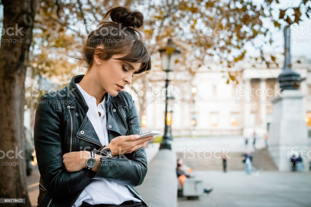 Besorgt Frau mit Smartphone am Trafalgar Square in London, Herbstsaison Lizenzfreies stock-foto
