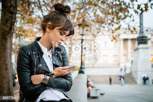 Beautiful, pensive woman wearing leather jacket sitting at Trafalgar Square in London and using smart phone, waiting for someone. Autumn season. National Gallery in the background.