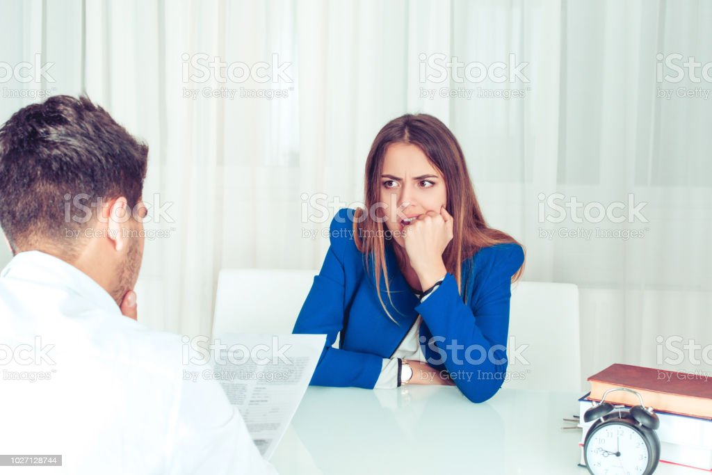 Worried woman with boss reading report Young nervous woman watching adult man reading paper document of resume at table in office. Anonymous man reading paperwork cv, contract female candidate for vacancy biting fist in stress and worries. Adult Stock Photo