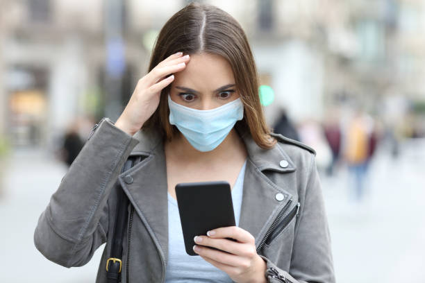 Worried woman with mask checking phone on street stock photo