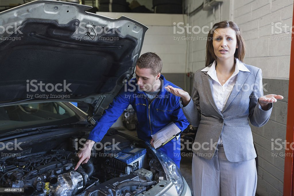 Worried woman with mechanic working on car at garage royalty-free stock photo
