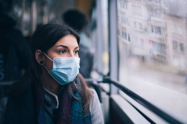 Worried Woman With Protective Face Mask In Bus Transport. Young woman wearing protective face mask, she sitting in bus transportation in the city. covid mask stock pictures, royalty-free photos & images