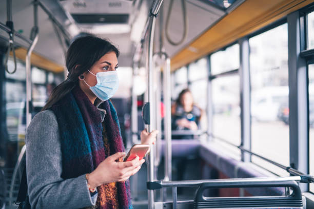 Worried Woman With Protective Face Mask In Bus Transport, Using Smart Phone