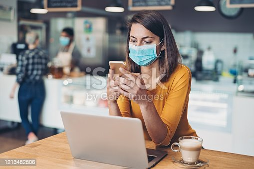 Woman wearing a face mask working on a laptop in cafe
