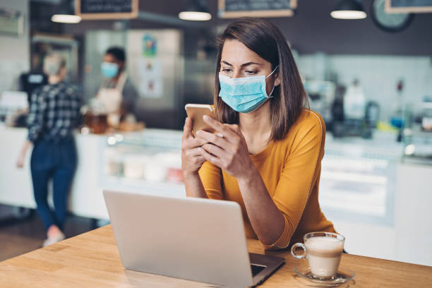 Worried woman with protective mask, cell phone and laptop stock photo