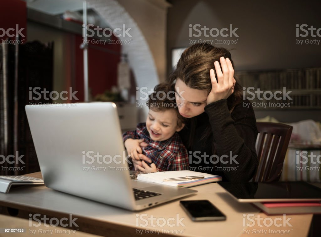 Worried woman working at home and holding her crying little son stock photo