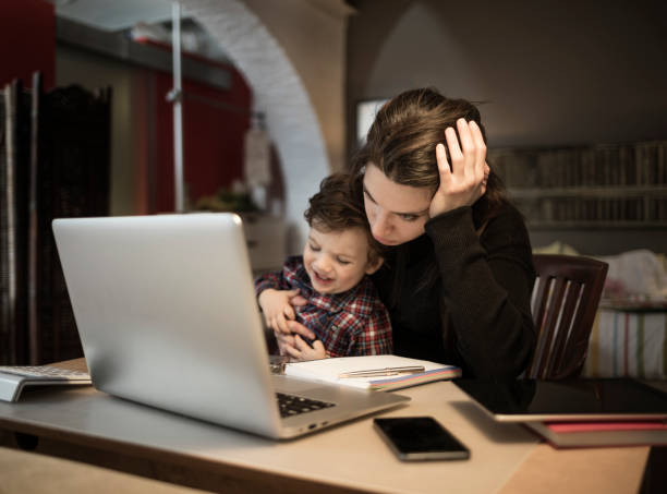 worried woman working at home and holding her crying little son - aluxum stock pictures, royalty-free photos & images