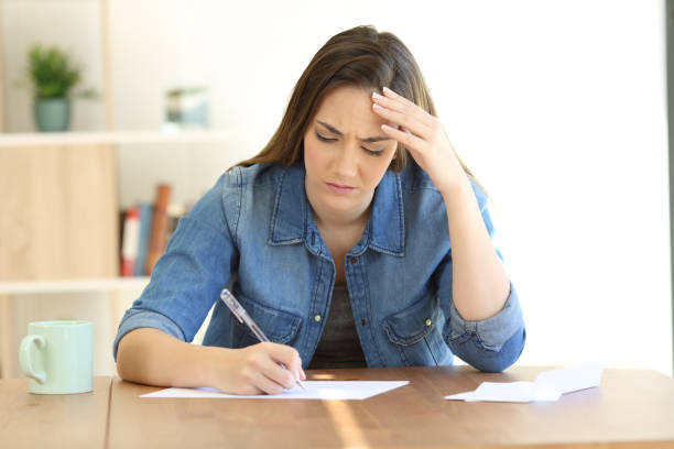 Worried woman writing a letter at home stock photo