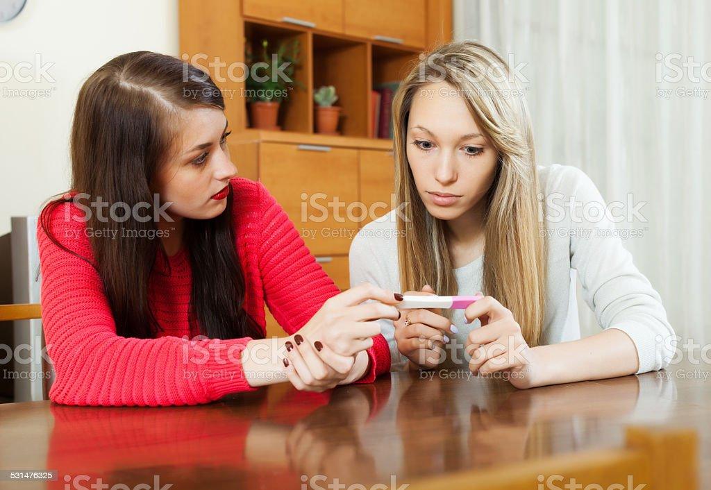 worried women with pregnancy test stock photo