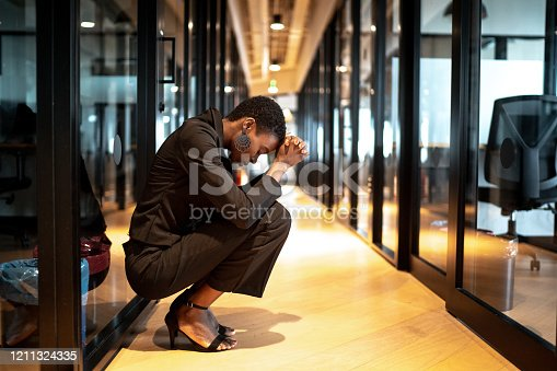 istock Worried young businesswoman at corridor office 1211324335