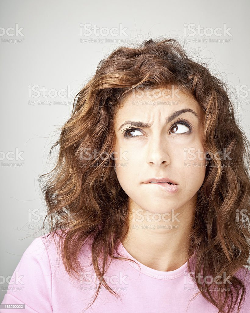Worried young girl biting lip stock photo