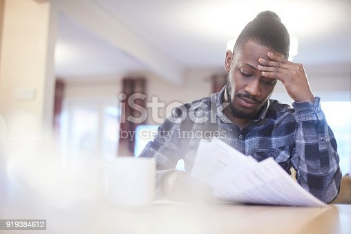 istock Worried young male reading through bank statements 919384612