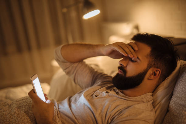 Worried young man reading bad news on smart phone stock photo