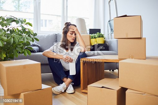 istock Worried young woman looking at bill sitting on floor in new apartment after moving in 1030219416