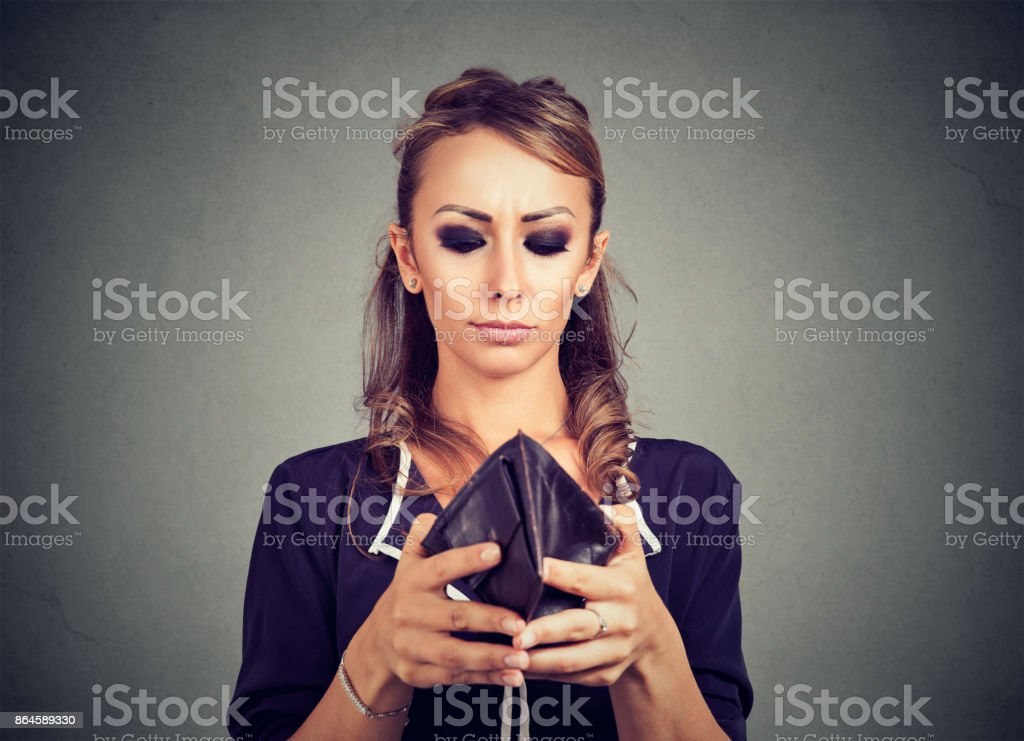 Worried young woman looking into her empty wallet stock photo
