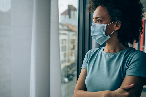 Worried young woman looking through window at home in quarantine.