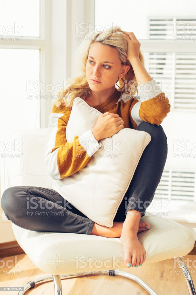 Worried young woman sitting in chair at home stock photo