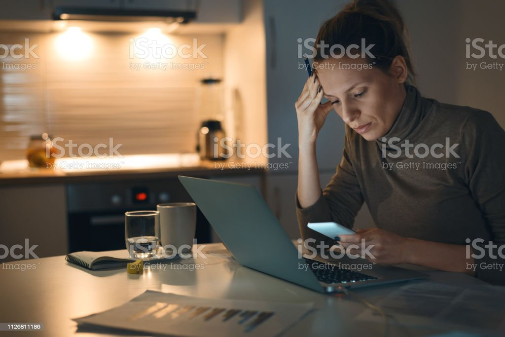 Worried young woman using cell phone while working at home Pensive young  woman using cell phone while working on laptop at home Adult Stock Photo