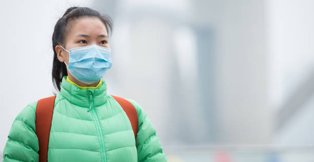 Worried young woman wear a face mask at the pollution city stock photo