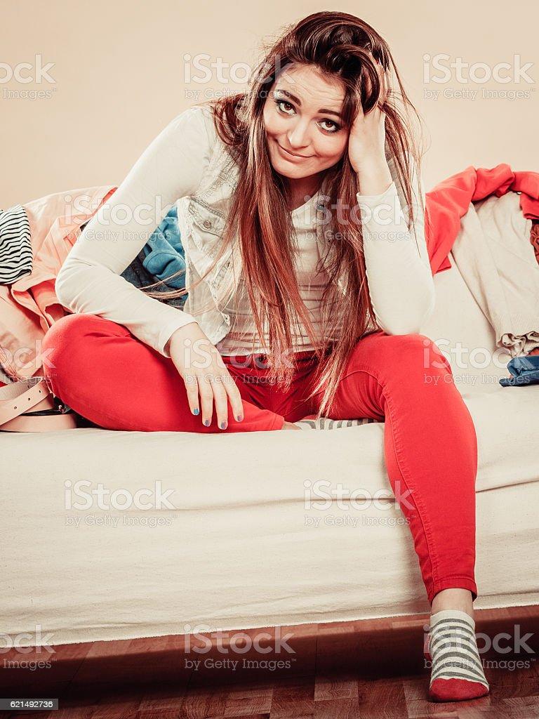 Preoccupato giovane donna con divano pieno di vestiti. foto stock royalty-free