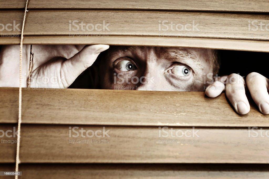 Worried-looking man peeps sideways through venetian blind stock photo
