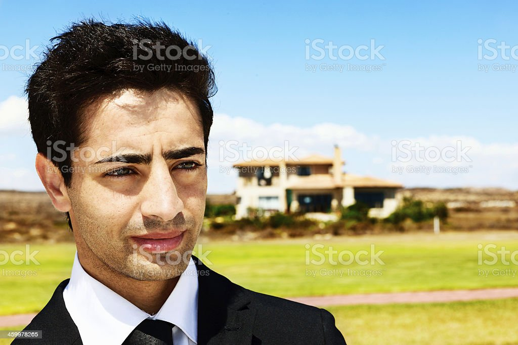 Worried-looking young man in formal clothes stands outside royalty-free stock photo