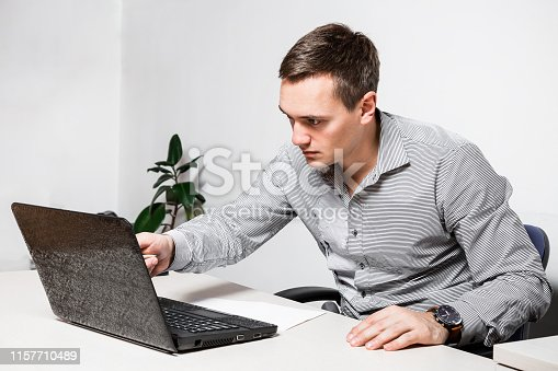 932342408istockphoto Worry businessman using laptop while sitting in office. Indicates a pen on the screen, reads important documents. 1157710489