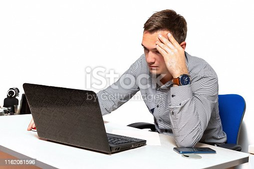 932342408istockphoto Worry businessman using laptop while sitting in office. pensive office worker with headache 1162081596