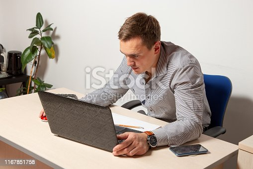 932342408istockphoto Worry businessman using laptop while sitting in office. pensive office worker 1167851758