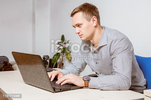 932342408istockphoto Worry businessman using laptop while sitting in office. Worker typing email on computer 1157710481