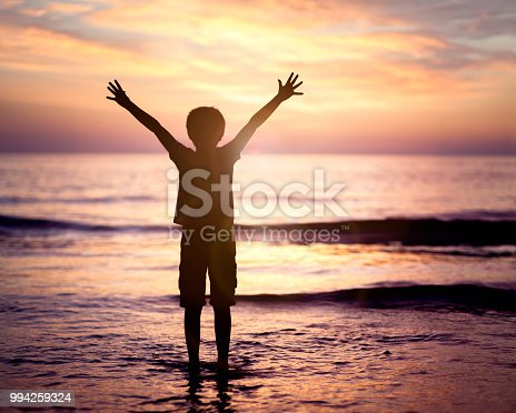 Silhouette of a boy with hands raised in the sunset over the sea concept for religion, worship, prayer and praise