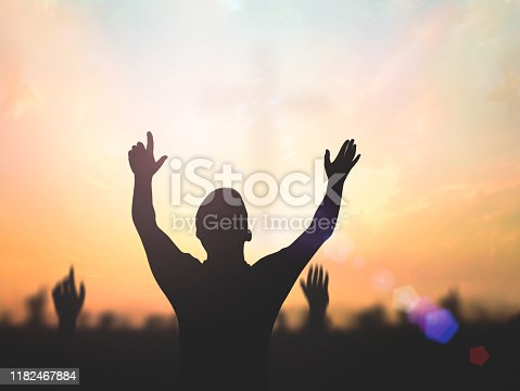 Silhouette christian people hand rising over blurred cross on spiritual light background