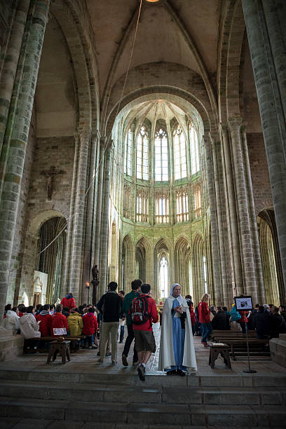 Worship at abbey church on Mont Saint-Michel, France Mont Saint-Michel, France - May 11, 2014: People prepare to worship on a Sunday morning inside the abbey church of Mont Saint-Michel, located in Normandy, France. abbey monastery stock pictures, royalty-free photos & images
