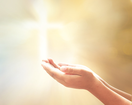 Prayer open empty hands with palm up over blurred cross with golden light background