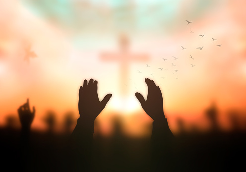 Silhouette christian hand rising over blurred cross on spiritual light background