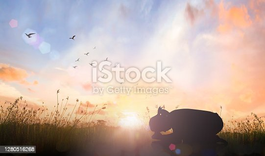 Silhouette woman christian bow down for worship God on meadow sunset background