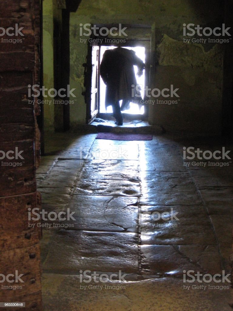 Worshipper stoops through low doorway to exit the Church of the Nativity in Bethlehem, Palestine stock photo