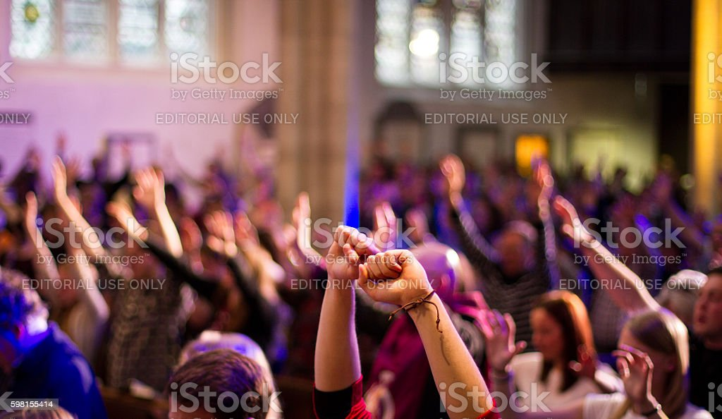 Worshippers raise their hands at a Christian church service stock photo