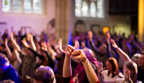 worshippers raise their hands at a christian church service - praise and worship stock photos and pictures