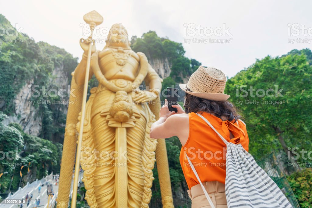 Worth remembering Female tourist taking photos of the golden statue in front of the Batu Caves Admiration Stock Photo