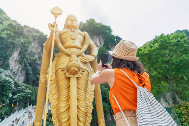 Worth remembering Female tourist taking photos of the golden statue in front of the Batu Caves kuala lumpur batu caves stock pictures, royalty-free photos & images