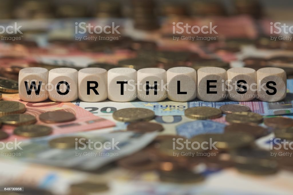 worthless - cube with letters, money sector terms - sign with wooden cubes stock photo