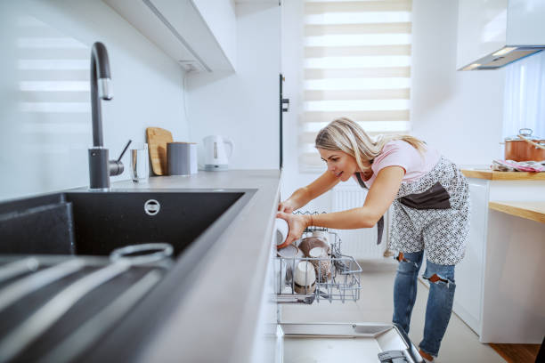 Worthy caucasian blond housewife in apron standing in domestic kitchen and putting dishes in dishwasher. Worthy caucasian blond housewife in apron standing in domestic kitchen and putting dishes in dishwasher. dishwasher stock pictures, royalty-free photos & images