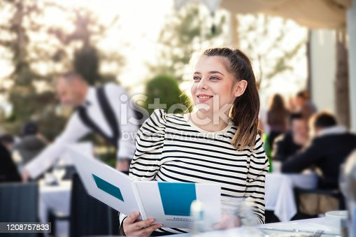 Young girl sitting at a restaurant, smiling and looking at the menu.