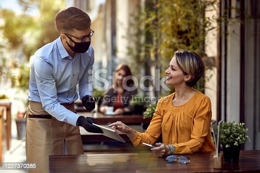 Happy woman talking to a waiter who is wearing protective face mask while choosing something from a menu on touchpad in a cafe.