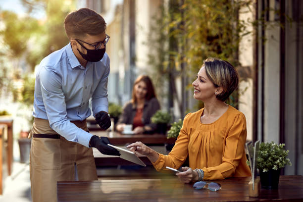 I would like to order this! Happy woman talking to a waiter who is wearing protective face mask while choosing something from a menu on touchpad in a cafe. restaurants stock pictures, royalty-free photos & images
