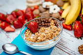 Fresh organic strawberries, bananas, nuts, cinnamon and bowl of mixed cereals and corn-flakes. Image taken with Nikon D800 and 50mm or 85 mm professional Nikon lens, developed from RAW and distributed in XXXL size. Location: Europe