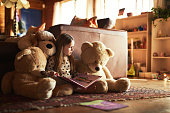 Shot of a little girl reading a book with her teddy bears around her