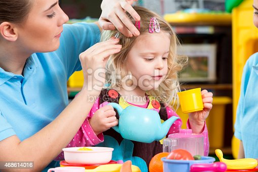 A horizontal image of a preschool child and teacher playing with a toy tea set. The teachers wears a blue polo shirt and the child is dressed casually pretending to pour tea out of a tea pot. The teacher is supervising the child and clipping her hair up