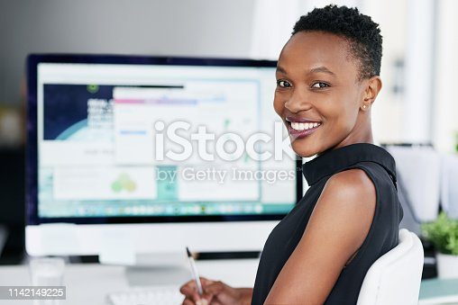 Shot of a confident young businesswoman using a computer in a modern office